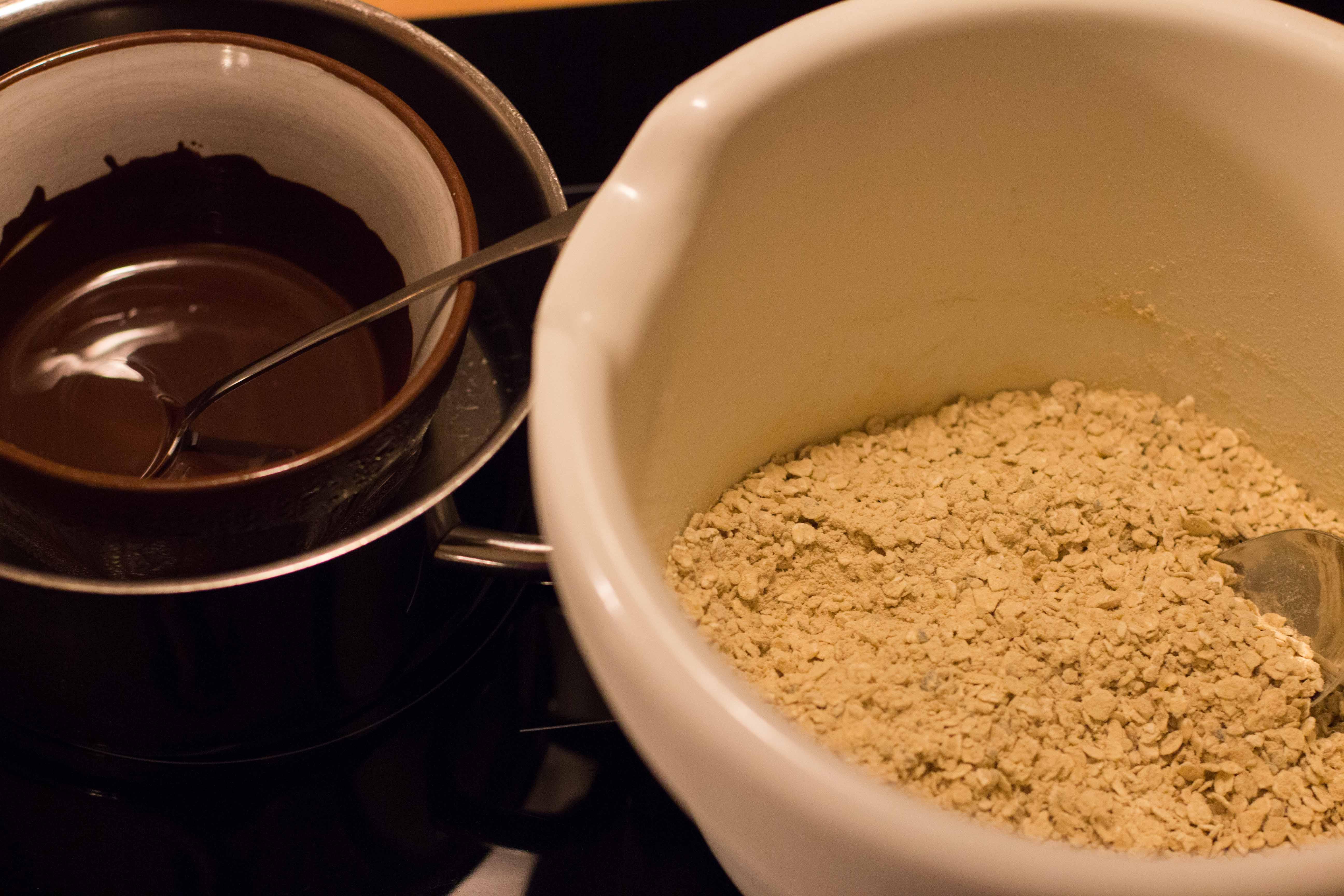 Proteinriegel-Zutaten: Schüssel mit trockenen Zutaten und geschmolzene Zartbitter Schokolade